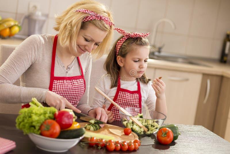 Moeder en dochter die salade maken stock afbeelding
