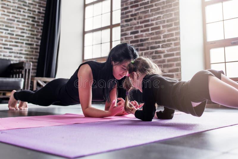 Moeder en dochter die samen het doen van plankoefening uitwerken in sportclub stock foto's