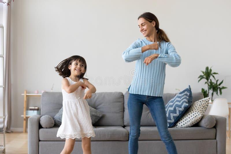 Moeder en dochter die samen in woonkamer dansen stock fotografie