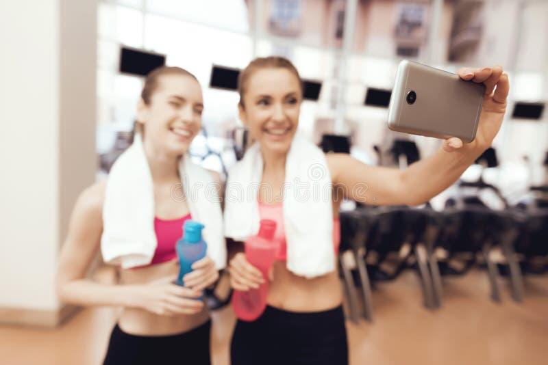 Moeder en dochter die selfie bij de gymnastiek nemen Zij kijken gelukkig, modieus en geschikt stock fotografie
