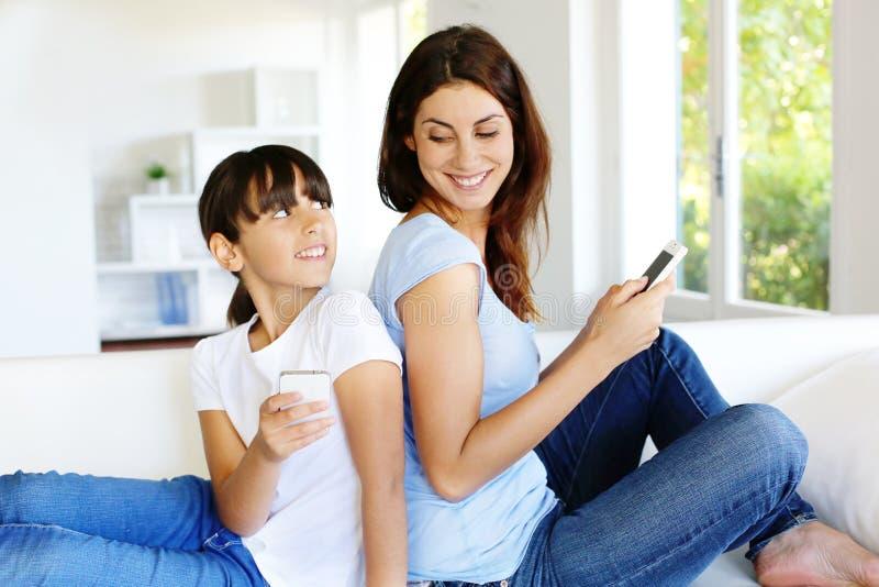 Moeder en dochter die smartphones gebruiken stock foto