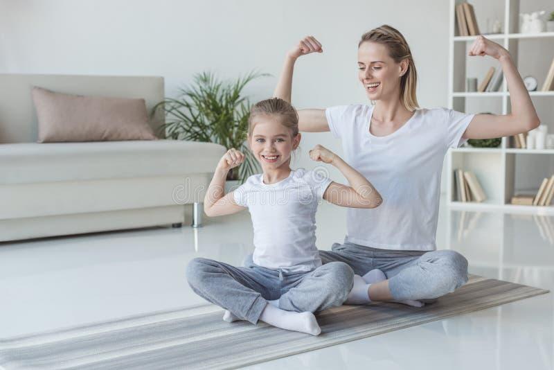 moeder en dochter die spieren tonen stock afbeelding