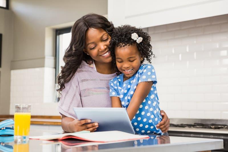 Moeder en dochter die tablet gebruiken stock foto's