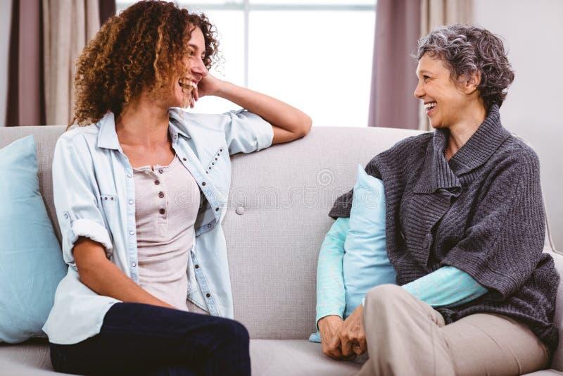 Moeder en dochter die terwijl het zitten op bank lachen royalty-vrije stock afbeelding