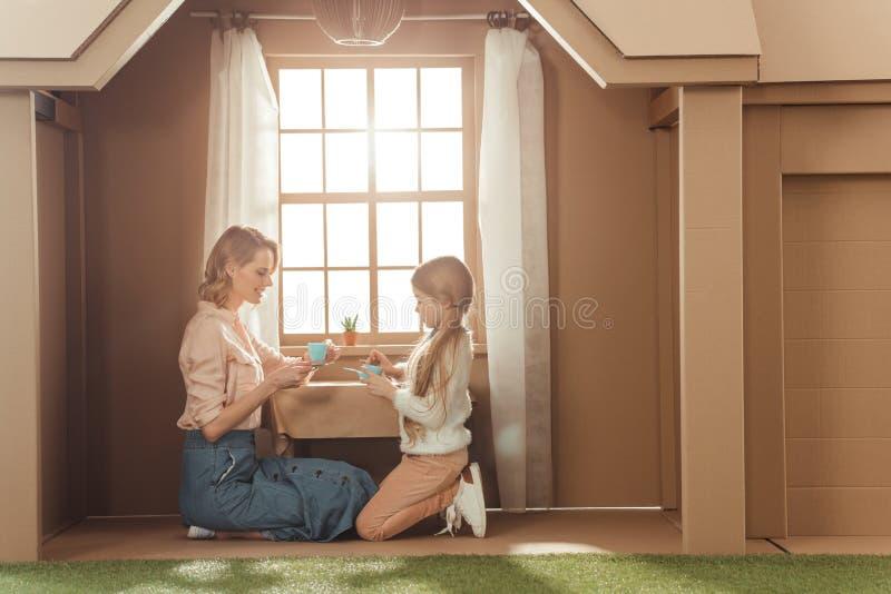 moeder en dochter die theekransje in kartonhuis hebben royalty-vrije stock afbeeldingen
