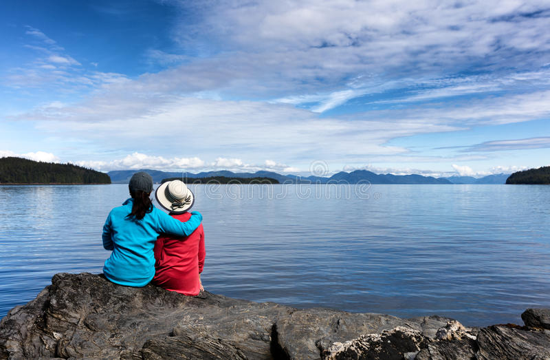 Moeder en dochter die van aard op het meer genieten stock fotografie