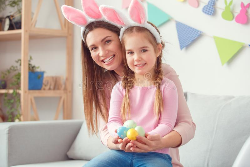 Moeder en dochter die in van de de vieringszitting van Pasen van konijntjesoren samen thuis de holdingseieren camera kijken stock fotografie