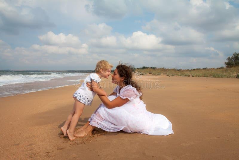 Moeder en dochter die van tijd genieten bij strand stock fotografie