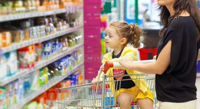 Moeder en dochter die voor kruidenierswinkels in supermarkt winkelen royalty-vrije stock afbeeldingen