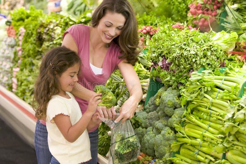 Moeder en dochter die voor opbrengst winkelen stock afbeelding