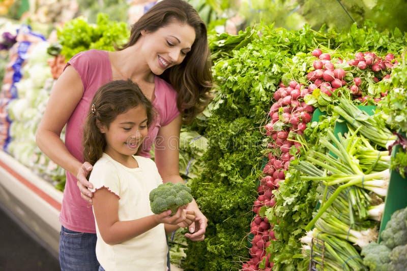 Moeder en dochter die voor verse opbrengst winkelen stock foto's