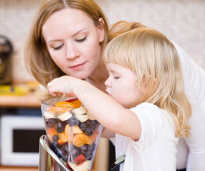 Moeder en dochter die vruchten eten stock afbeeldingen