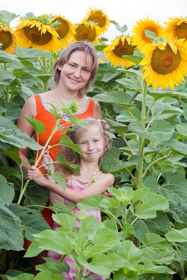 Moeder en dochter die zich bij zonnebloemengebied bevinden stock afbeeldingen
