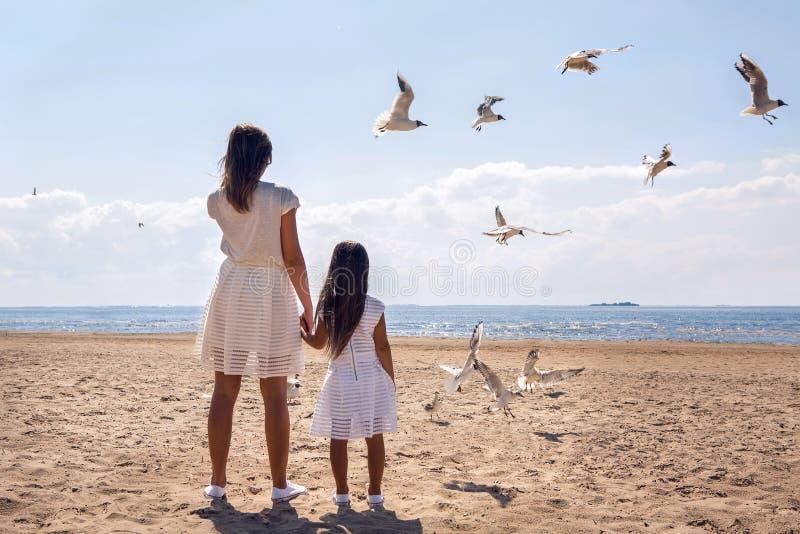 Moeder en dochter die zich op het strand bevinden stock afbeelding