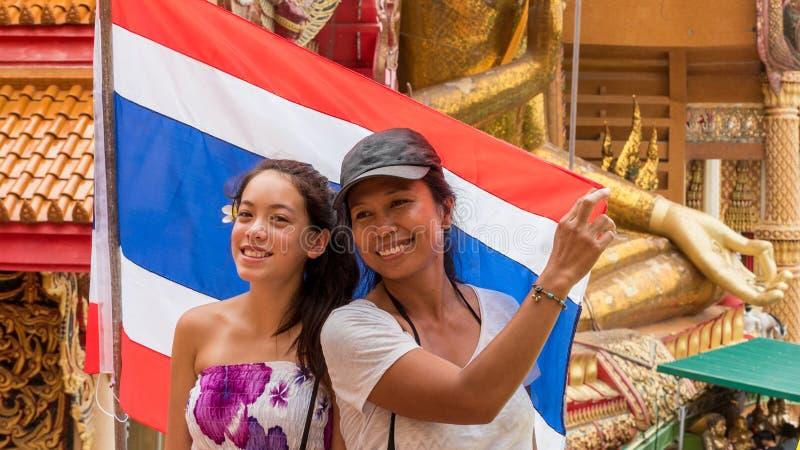 Moeder en dochter die zich voor vlag bevinden stock foto