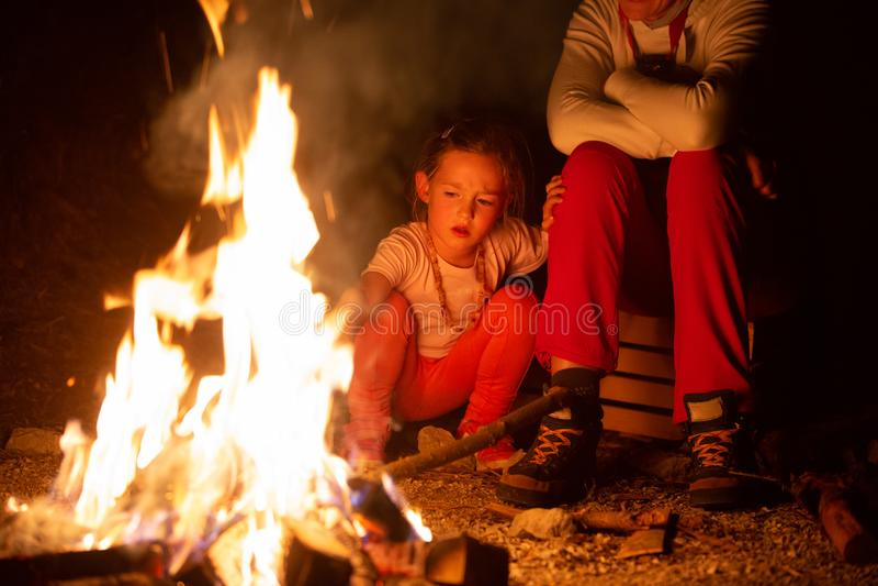 Moeder en dochter het besteden kwaliteitstijd door een zelf-gemaakt kampvuur tijdens avontuurlijke het kamperen reis, die met bra stock afbeelding