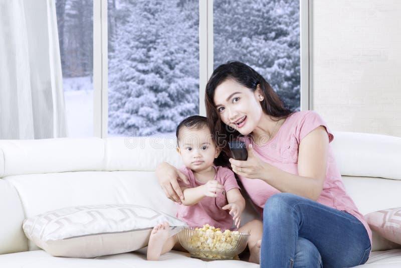 Moeder en dochter het besteden tijd met televisie stock afbeeldingen