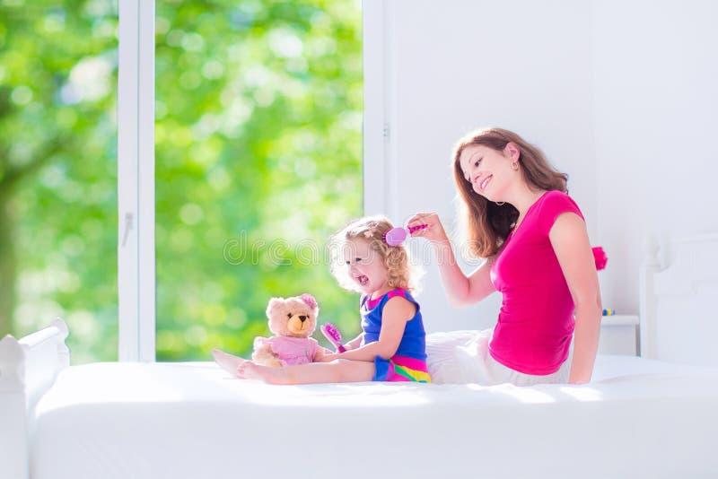 Moeder en dochter het borstelen haar stock foto