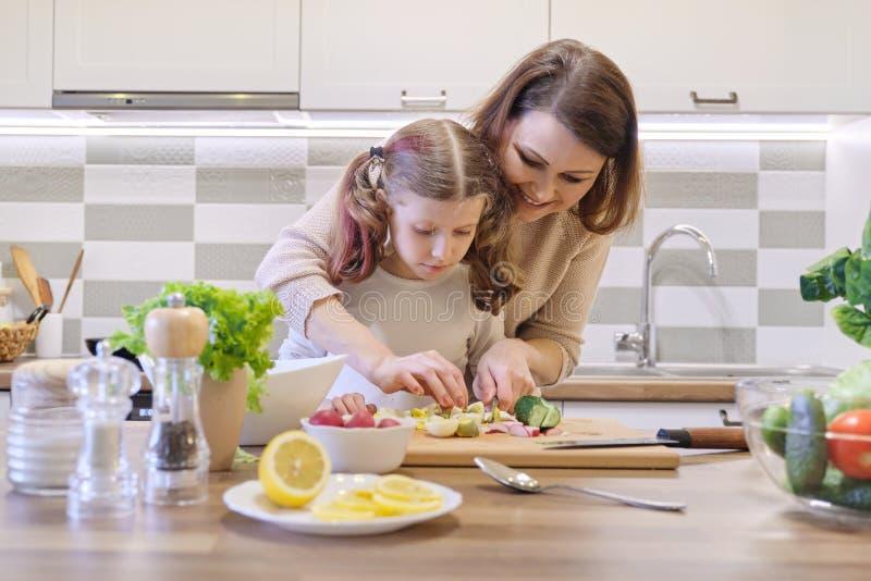 Moeder en dochter het koken samen in keuken plantaardige salade, ouder en kind spreekt het glimlachen stock fotografie