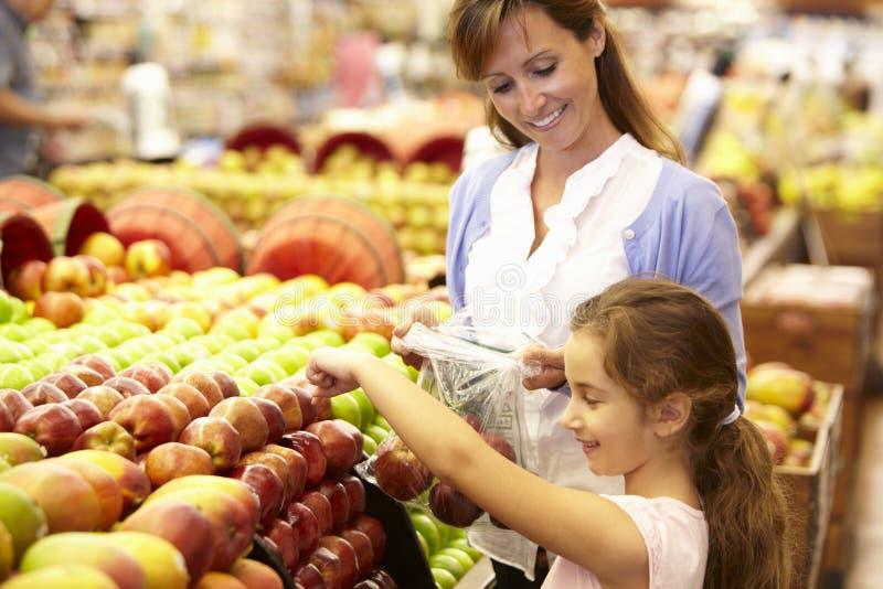 Moeder en dochter het kopen fruit in supermarkt royalty-vrije stock fotografie
