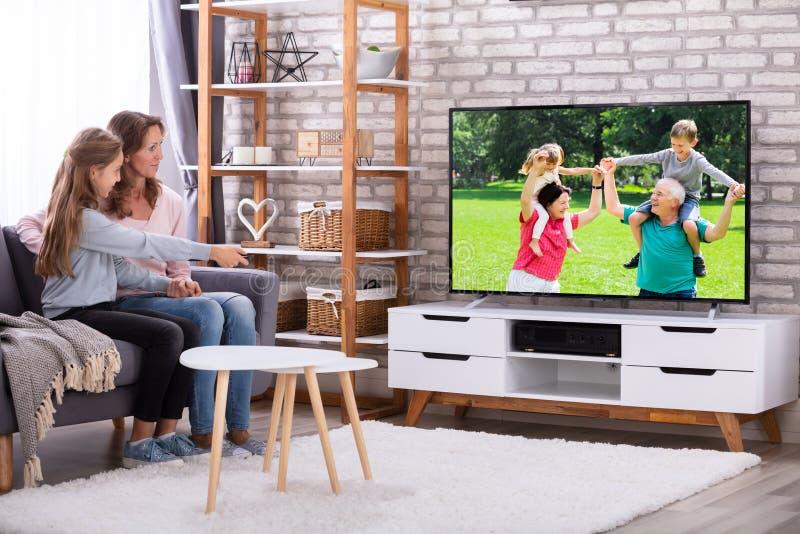 Moeder en dochter het letten op televisie in woonkamer stock foto