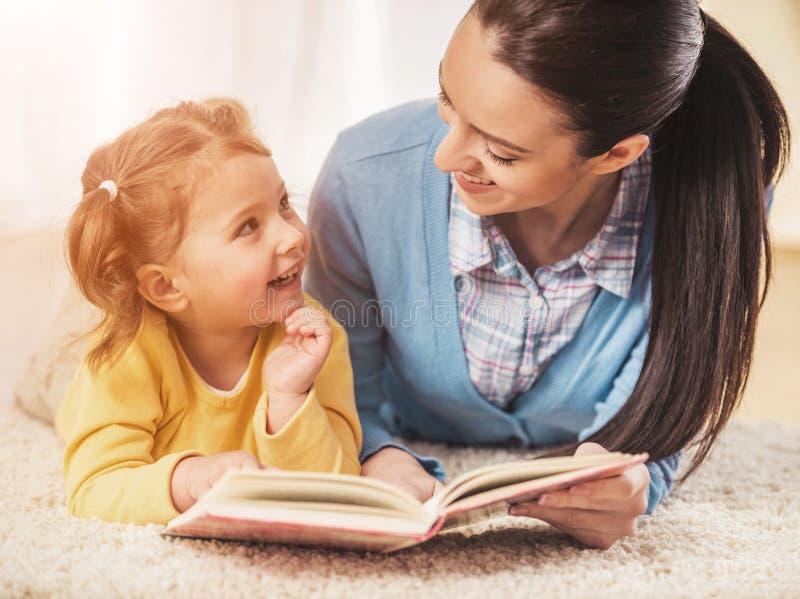 Moeder en Dochter het Lezingsboek en ligt op Tapijt royalty-vrije stock fotografie