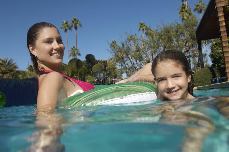 Moeder en Dochter het Ontspannen op Opblaasbaar Vlot in Zwembad royalty-vrije stock fotografie