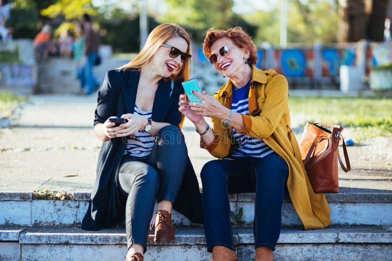 Moeder en dochter in het park die inhoud op smartphone delen stock foto's