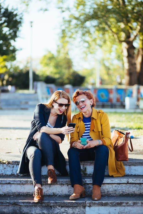 Moeder en dochter in het park die inhoud op smartphone delen stock afbeeldingen
