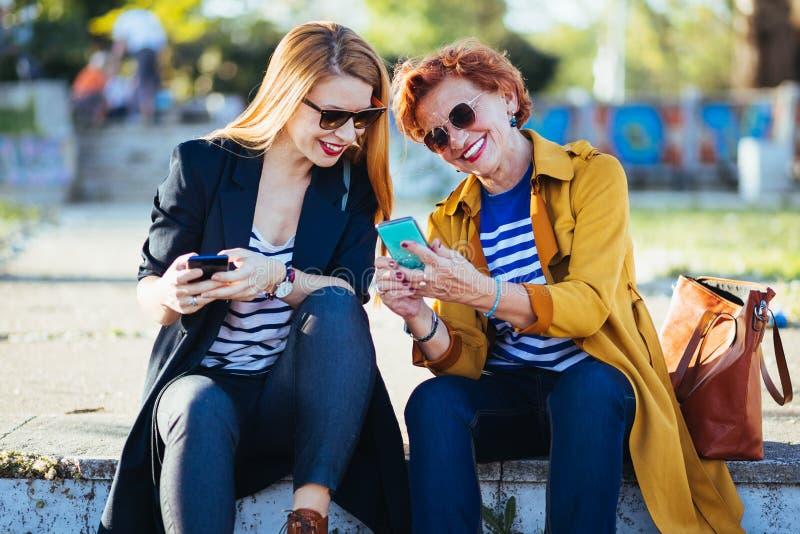 Moeder en dochter in het park die inhoud op smartphone delen royalty-vrije stock foto