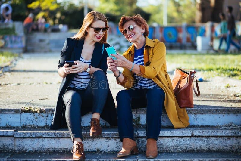 Moeder en dochter in het park die inhoud op smartphone delen royalty-vrije stock foto's