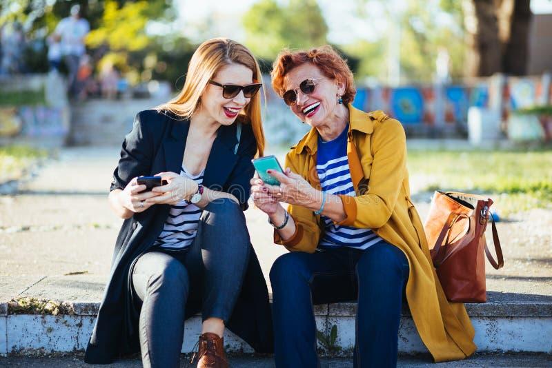 Moeder en dochter in het park die inhoud op smartphone delen royalty-vrije stock afbeeldingen