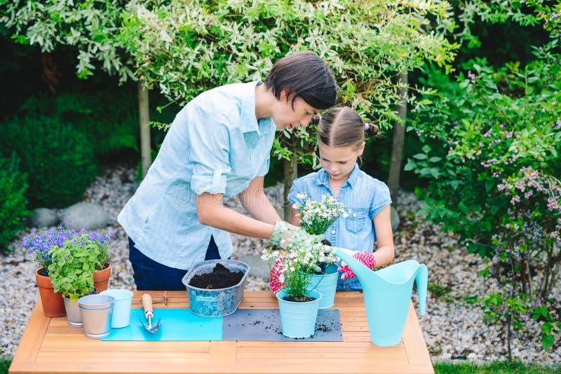 Moeder en dochter het planten bloeit in potten in de tuin - concept het samenwerken, nabijheid royalty-vrije stock afbeelding