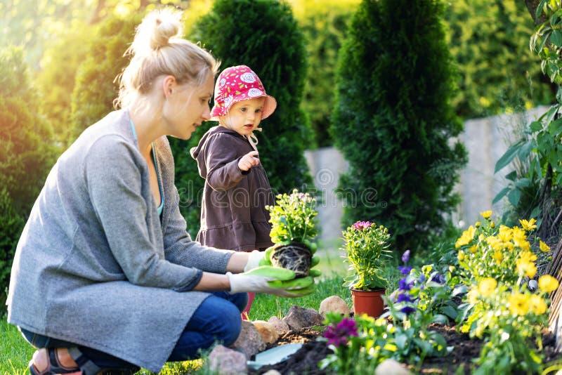 Moeder en dochter het planten bloeit samen stock afbeelding