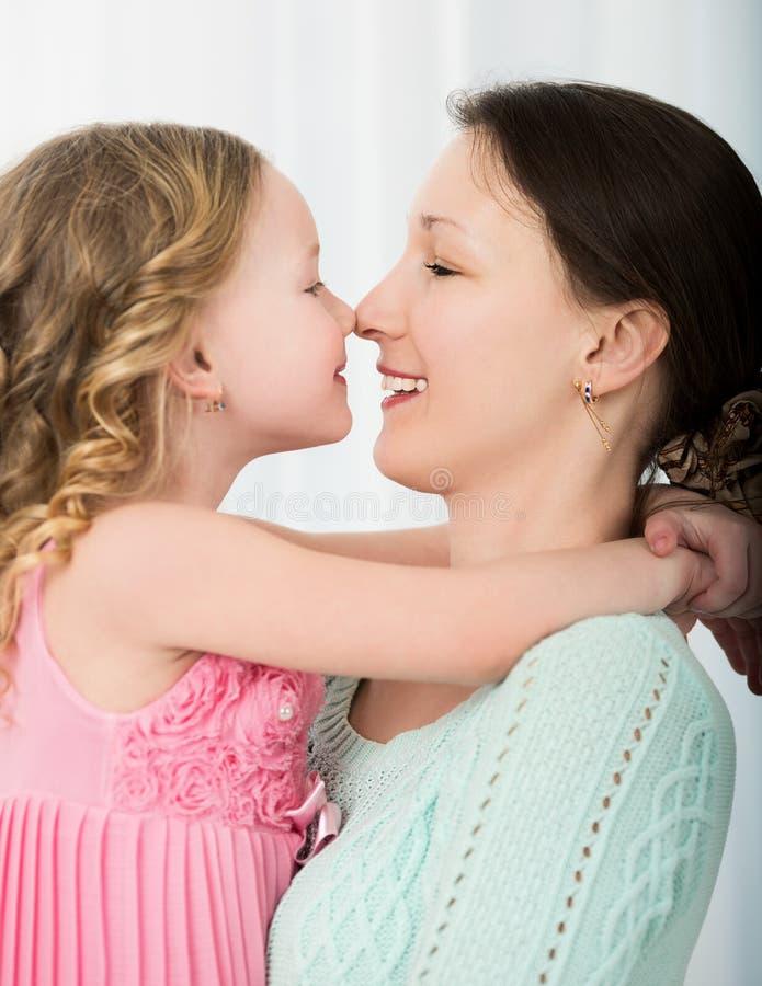Moeder en dochter het raken met neuzen stock afbeelding
