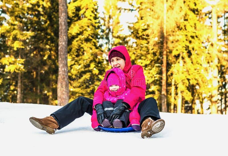 Moeder en dochter het sledding in de winter stock fotografie