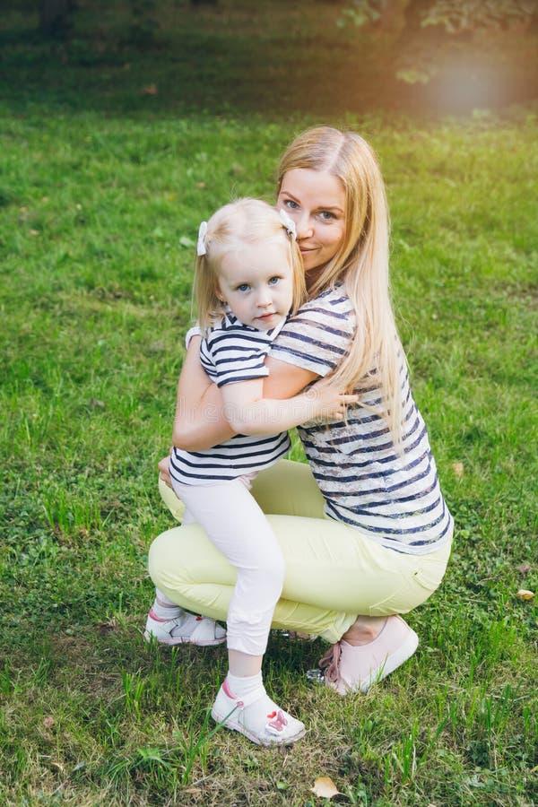 Moeder en dochter het spelen in de weide stock foto