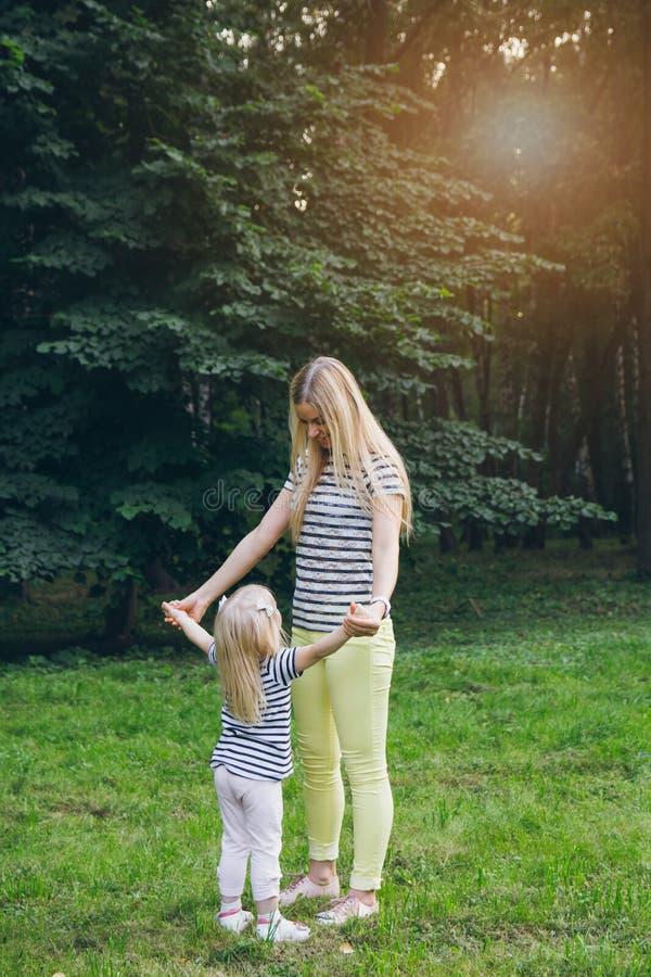 Moeder en dochter het spelen in de weide stock fotografie