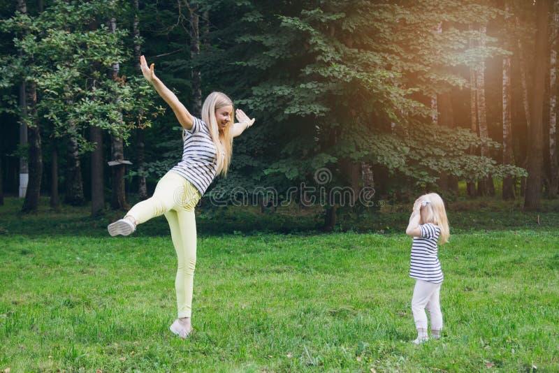 Moeder en dochter het spelen in de weide stock foto's