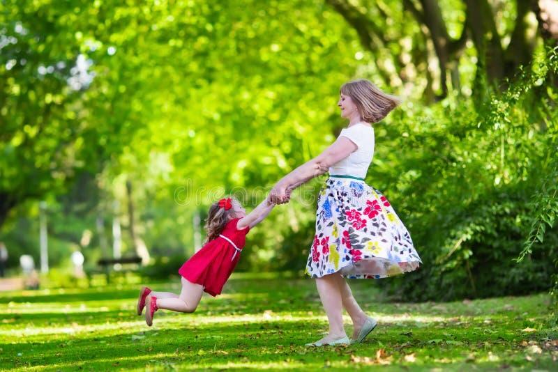 Moeder en dochter het spelen in een park royalty-vrije stock afbeeldingen