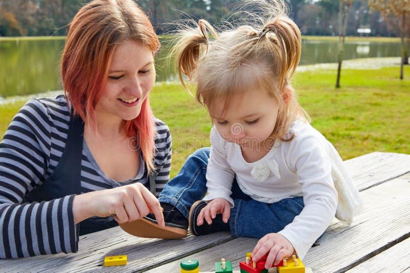 Moeder en dochter het spelen met vormen in park royalty-vrije stock foto's