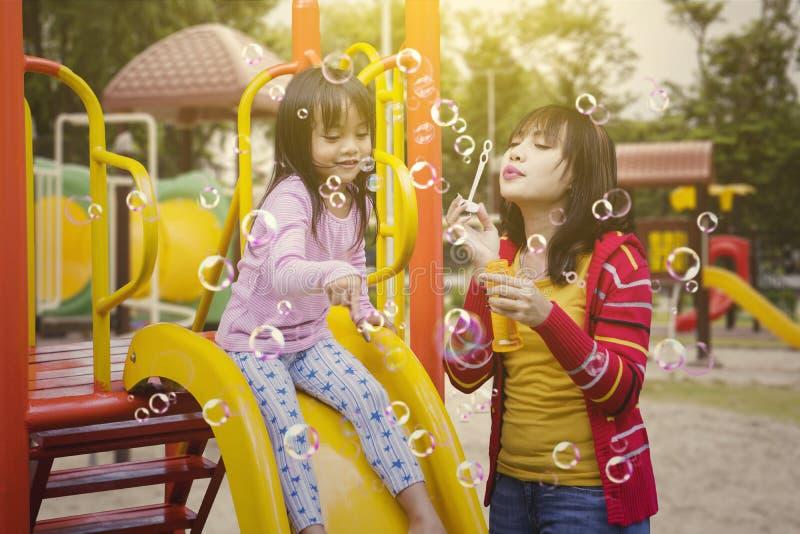 Moeder en dochter het spelen met zeepbels royalty-vrije stock foto