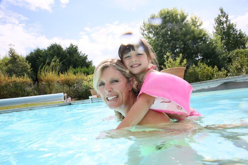Moeder en dochter het spelen in pool stock foto