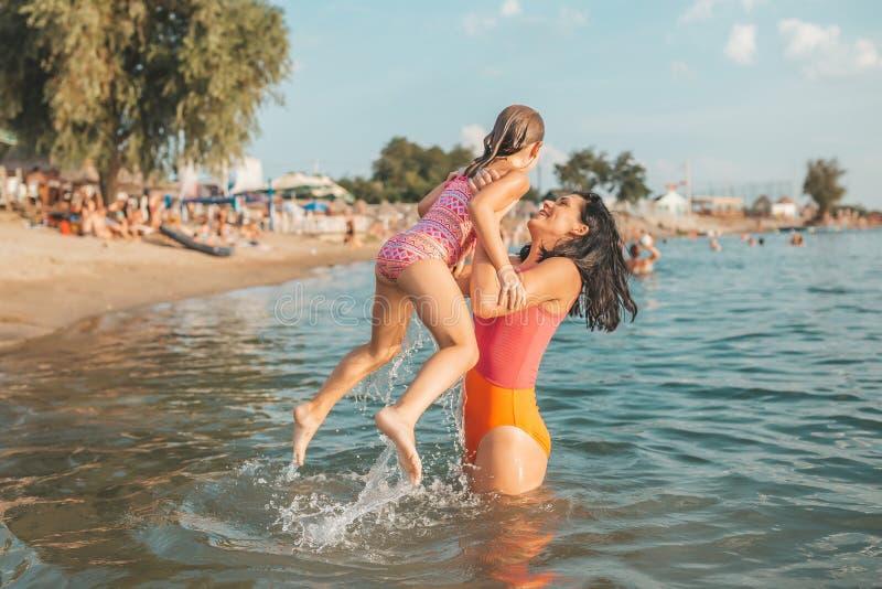 Moeder en dochter het spelen in het water royalty-vrije stock fotografie