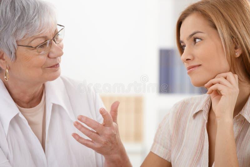 Moeder en dochter het spreken het glimlachen royalty-vrije stock afbeelding