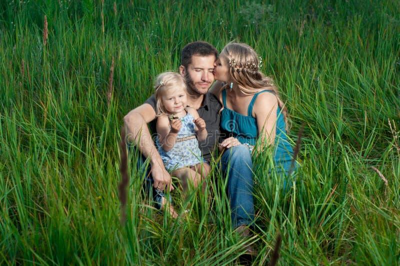 Moeder en dochter kussende papa in openlucht royalty-vrije stock foto