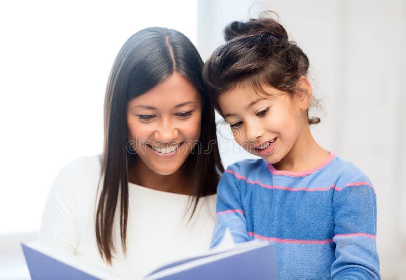 Moeder en dochter met boek stock afbeelding