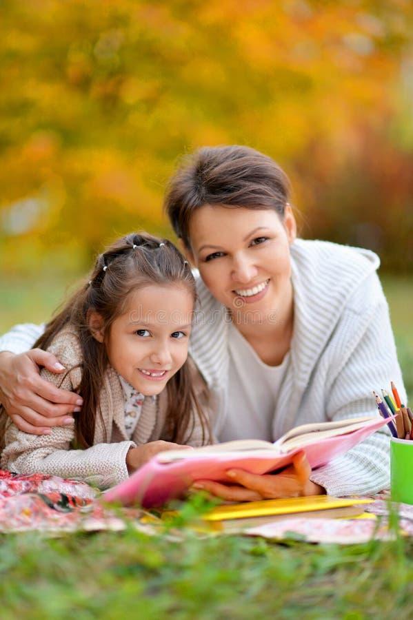 Moeder en dochter met boeken in park royalty-vrije stock foto's