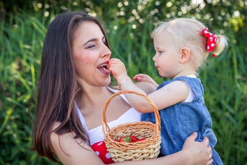 Moeder en dochter met een aardbei royalty-vrije stock fotografie