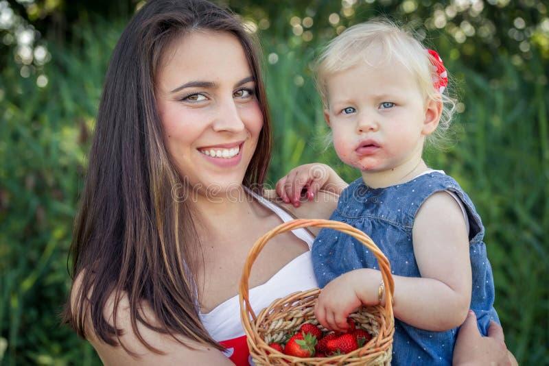 Moeder en dochter met een aardbei royalty-vrije stock foto's